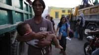 Un père et son fils s'apprêtent à évacuer la ville d'Esperanza (sud des Philippines) dans une zone attaquée par les rebelles des Combattants pour la liberté du Bangsamoro islamique (Biff), le 1er janvier 2016.