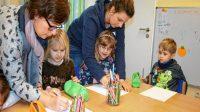 La démocratie de l'enfance: les éducateurs Marion Maaβ et Tina Westphal aident les enfants à copier le protocole pour leurs groupes respectifs.