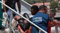 Un volontaire aidant un migrant à son arrivée au Port de Salerno, Italie,le 29 juin 2017.