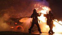 Des pompiers éteignent une voiture en feu dans le quartier de la Meinau à Strasbourg durant la nuit du nouvel an