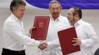 Le président colombien Juan Manuel Santos et le chef des FARC connu sous le nom de Timochenko, sous le regard du président cubain Raul Castro à la Havane lors de la signature de l'accord de paix historique le 23 juin 2016.