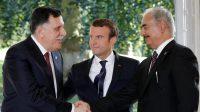 Le Premier ministre libyen Fayez al-Sarraj (g) et le général Khalifa Haftar, chef d'une force baptisée Armée nationale libyenne (ANL), se serrent la main devant le président français Emmanuel Macron, à Celle-Saint-Cloud, près de Paris, le 25 juillet 2017.